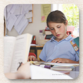 schoolgirl concentrating on reading in class beverage coaster
