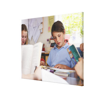 schoolgirl concentrating on reading in class canvas print