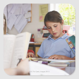 schoolgirl concentrating on reading in class square sticker