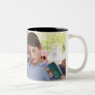 schoolgirl concentrating on reading in class Two-Tone coffee mug
