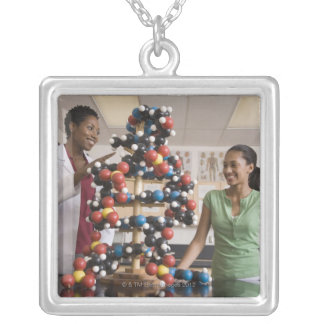 Science teacher and teenage girl looking at necklaces