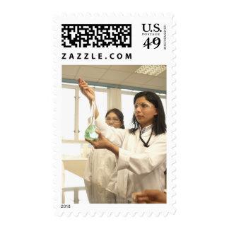 Scientist adding solution to beaker postage stamp