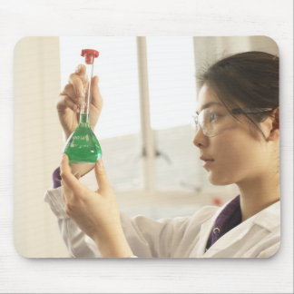 Scientist examining liquid in beaker mouse pad