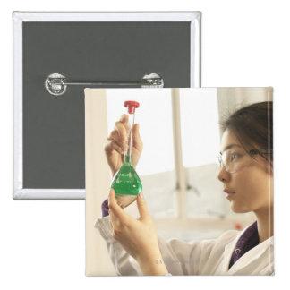 Scientist examining liquid in beaker pinback button