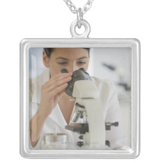 Scientist using microscope in pharmaceutical silver plated necklace