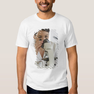Scientist using microscope in pharmaceutical t-shirt