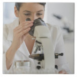 Scientist using microscope in pharmaceutical tiles