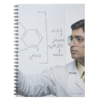 Scientist writing chemical formula notebook