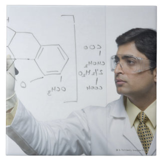 Scientist writing chemical formula tile