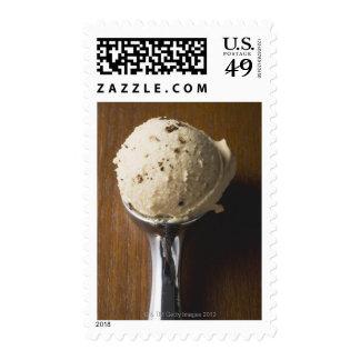 Scoop of ice cream in ice cream scoop (overhead postage stamps