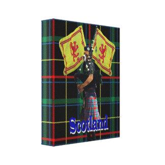 Scottish piper on tartan canvas print