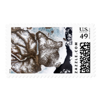 Sea ice lines the shoreline in eastern Greenlan Postage Stamp
