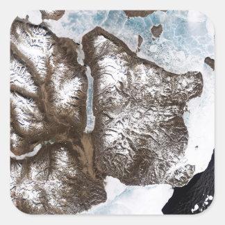 Sea ice lines the shoreline in eastern Greenlan Square Sticker