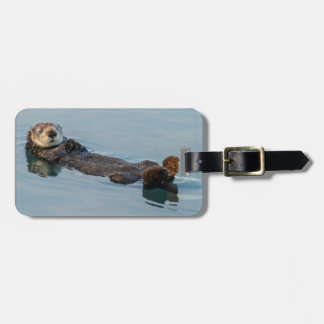 Sea otter floating on back in ocean tag for luggage