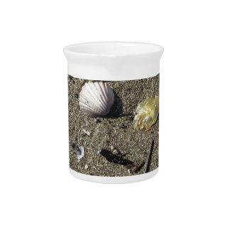 Sea shells on sand. Summer beach background Drink Pitcher
