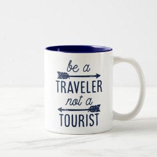 Sea un viajero no una cita turística de la taza de café de dos colores