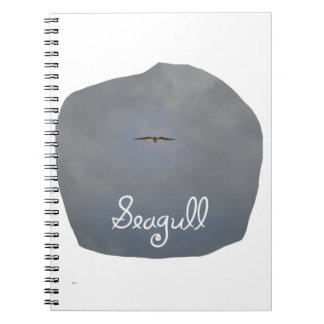Seagull flying in a grey sky with text Seagull Spiral Note Books