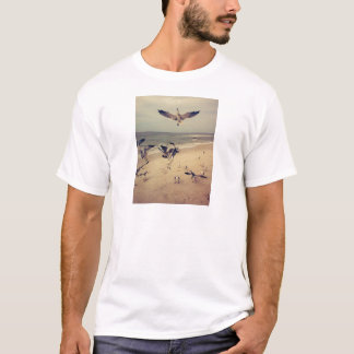 Seagulls flying on the beach T-Shirt