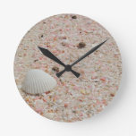 Seashell blanco en la playa rosada de la arena reloj de pared