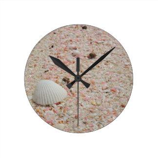 Seashell blanco en la playa rosada de la arena reloj redondo mediano