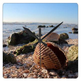Seashells en la playa en reloj de pared de la Flor