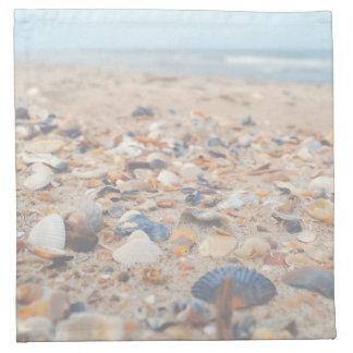Seashells en las servilletas del paño de la playa