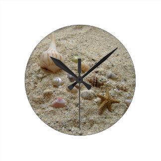 Seashells Nestled in Beach Sand Round Clock
