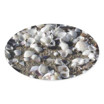 Beach Themed Seashells on sand. Summer beach background Oval Sticker