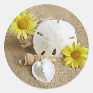 Seashells y arena de la margarita en foto en el pegatina redonda