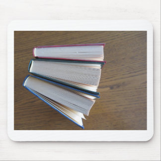 Second hand books standing on a wooden table mouse pad