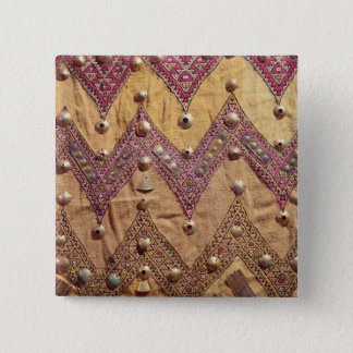 Section of embroidered fabric with gold plaques pinback button