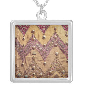Section of embroidered fabric with gold plaques silver plated necklace