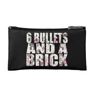Seis balas y un bolso del cosmético del ladrillo