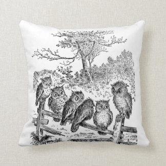 Seis pequeños búhos que se sientan en una cerca an almohada