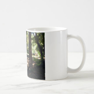 Selective focus on a young branch of a tree with l classic white coffee mug