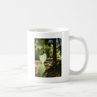 Selective focus on a young branch of a tree with l coffee mug