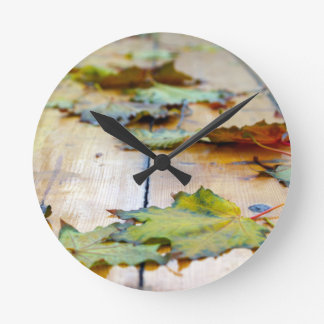 Selective focus on autumn maple leaves with shallo round wall clock