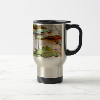Selective focus on autumn maple leaves with shallo travel mug