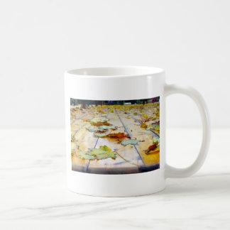 Selective focus on fallen autumn maple leaves clos coffee mug