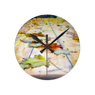 Selective focus on fallen autumn maple leaves clos round wall clocks