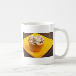 Selective focus on raw cashew nuts closeup coffee mug