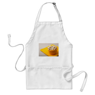 Selective focus on raw cashew nuts in a small cup adult apron