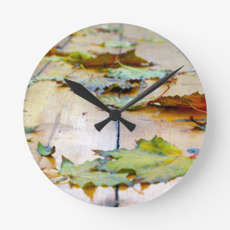 Selective focus on the autumn fallen maple leaves round clock