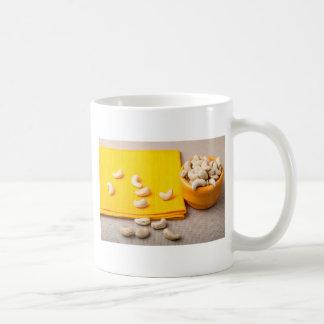 Selective focus on the tablecloth and raw cashew coffee mug