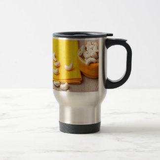 Selective focus on the tablecloth and raw cashew travel mug