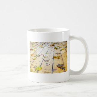 Selective focus on wet fallen autumn maple leaves coffee mug