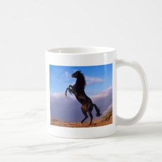 Semental negro salvaje que alza el caballo tazas