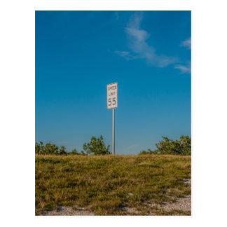Señal de tráfico en la colina y el cielo azul tarjeta postal