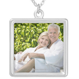 Senior Caucasian couple in robes in spa. Square Pendant Necklace