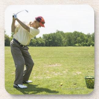 Senior golfer hitting practice balls at a range coaster